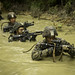 Marines navigate through an endurance course during a squad competition at the Jungle Warfare Training Center
