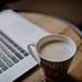 Cup of coffee near the Macbook closeup.