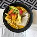 Veganes rotes Curry mit Reis und Gemüse in schwarzem Teller, Aufnahme von oben