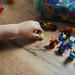 Little girl sorts Kinder toy in her room.