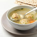 Bowl of Jewish matzoh balls soup on white wooden table