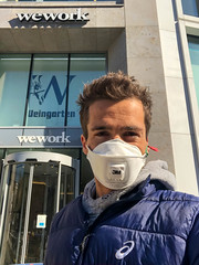 Coronavirus and WeWork. Man with FFP3 mask in front of office