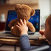 Little girl teaches teddy bear to work on laptop.