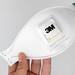 Hand hält eine Aura FFP3 Atemschutzmaske 9332+ von 3M vor weißem Hintergrund