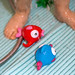 Close-up of colorful fish bathing toys. Toddler taking a shower