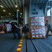 Marines and Sailors aboard amphibious assault ship USS America move supplies during a supply onload