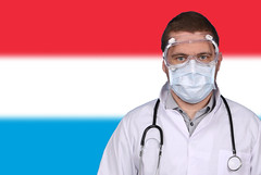Doctor in protective medical mask over flag of Luxembourg