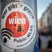 Sticker an einem Pfosten macht auf das gratis Public WLAN in Wien aufmerksam