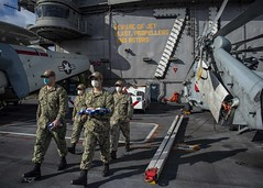 Sailors carry the American flag and union jack to conduct morning colors on the flight deck