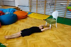 W leżeniu na plecach przenoszenie stóp na krzesło z trzymaniem rękami nóg krzesła (1/3)