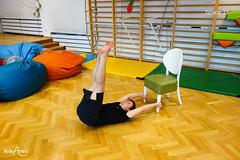 W leżeniu na plecach przenoszenie stóp na krzesło z trzymaniem rękami nóg krzesła (2/3)
