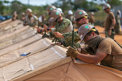 Sailors assemble a tent during construction of a 150-bed expeditionary medical facility at Naval Base Guam.