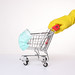 Hands in yellow protective gloves pushing shopping cart with protective face mask corona virus or Covid-19 protection