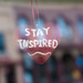 A heart with the words Stay Inspired hanging in a window in a window on Central Avenue in downtown Faribault, Minnesota