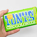Hand hält eine 100% sklavenfreie Tony's Chocolonely Schokoladentafel mit Mandeln und Meersalz. Grüne Packung vor weißem Hintergrund