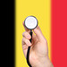 Hand holding stethoscope with flag of Belgium. Concept of medicine, virus, epidemic, vaccination.