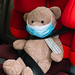 Teddy bear toy in a medical mask is sitting in a child seat in the car.