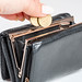Female hand puts coins in an open black wallet