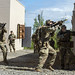Paratroopers react to simulated enemy contact while clearing buildings during squad training