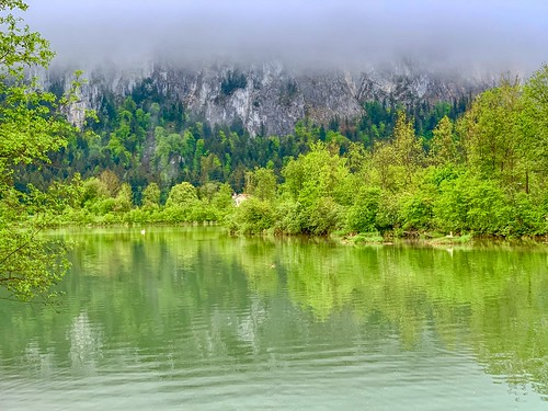 Kieferbach creek entering the river Inn with low clouds covering Zahmer Kaiser mountains in Kiefersfelden, Bavaria, Germany