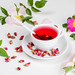 White cup of tea with dried and fresh tea rose flowers on a white background
