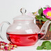Glass teapot with red tea and tea rose flowers on a white background