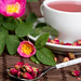 Dry tea rose buds in a spoon with a cup of tea and flowers behind
