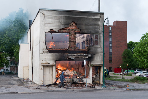 A man walks by a burning building on Thu by Lorie Shaull, on Flickr
