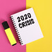 2020 Crisis text in notebook on colorful background