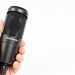 Black studio condenser microphone Audio Technica in the hand with copy space