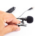 Lavalier Microphone in the hand above white background