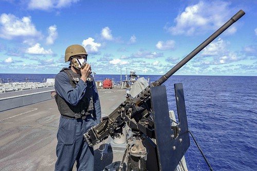 A Sailor mans an M240B machine gun aboard the Arleigh Burke-class guided-missile destroyer USS Russell