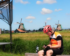 Sit | Biker resting and sitting at Zaanse Schans. Windmills in the background