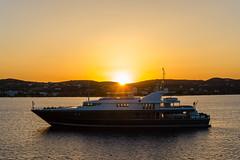 Eine Yacht und der Sonnenuntergang am Hafen von Adámas, Milos, Griechenland