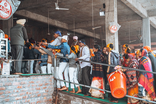Amritsar India - Febuary 8, 2020: Crowds of people walk into the free kitchen (Langar) to get food in the Sikh Golden Temple (sri harmandir sahib)
