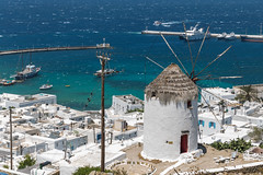 Ancient windmill, symbol of the Cyclades, overlooking Mykonos' main town Chora and harbour