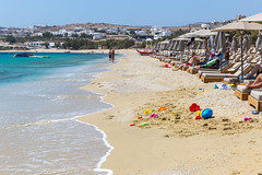 Beach sand toys by the seashore and tourists sunbathing at Kalafati beach, Mykonos, Greece