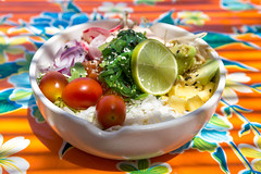 Salmon poke bowl with rice, lime, cherry tomatoes, radish, sprouts, avocado, herbs on a floral tablecloth