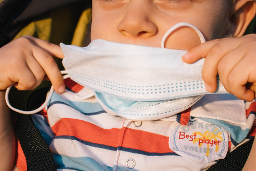 Toddler boy holding a medical face mask over his mouth