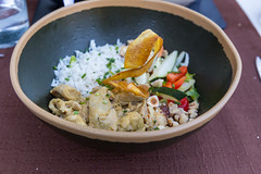 Country chicken curry Q11 style with seasonal vegetables and rice in a black bowl at Q11, Pollença