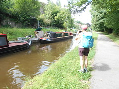 Photo of Llangollen Canal at Chirk Bank. Ronnie photographing sign on narrowboat.
