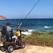 Angler auf Griechenland: Alter Mann sitzt mit seiner Angel im Elektromobil an der Küste der Insel Naxos