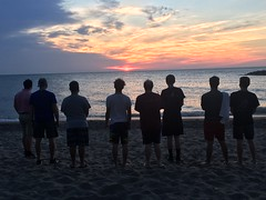 The seminarians and priests of St. Mark Seminary sing a Marian hymn at sunset at Presque Isle on August 14, 2020.