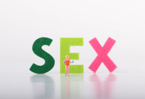 Miniature girl in swimwear stading in front of Sex text on white background