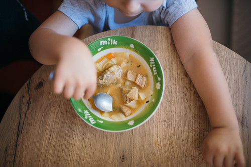 Young girl eating a plate of soup with a spoon in the kitchen.