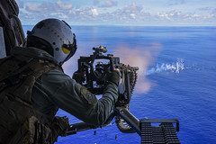 A naval air crewman fires a .50-caliber machine gun during a live-fire exercise.