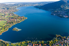 Aerial shot: Tegernsee lake in Bavaria with blue waters, the abbey, the island and towns on the shore