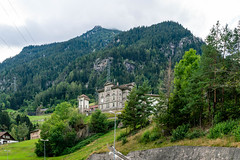 Big stone castle build on the slope of the hill overlooking mountains in Switzerland