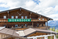 Das hölzerne Gebäude des Berggasthofs Hornboden mit dem grünen Schild und Hörnern als Symbol