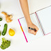 Woman writing on a notepad. Weight-loss planning with fresh vegetables